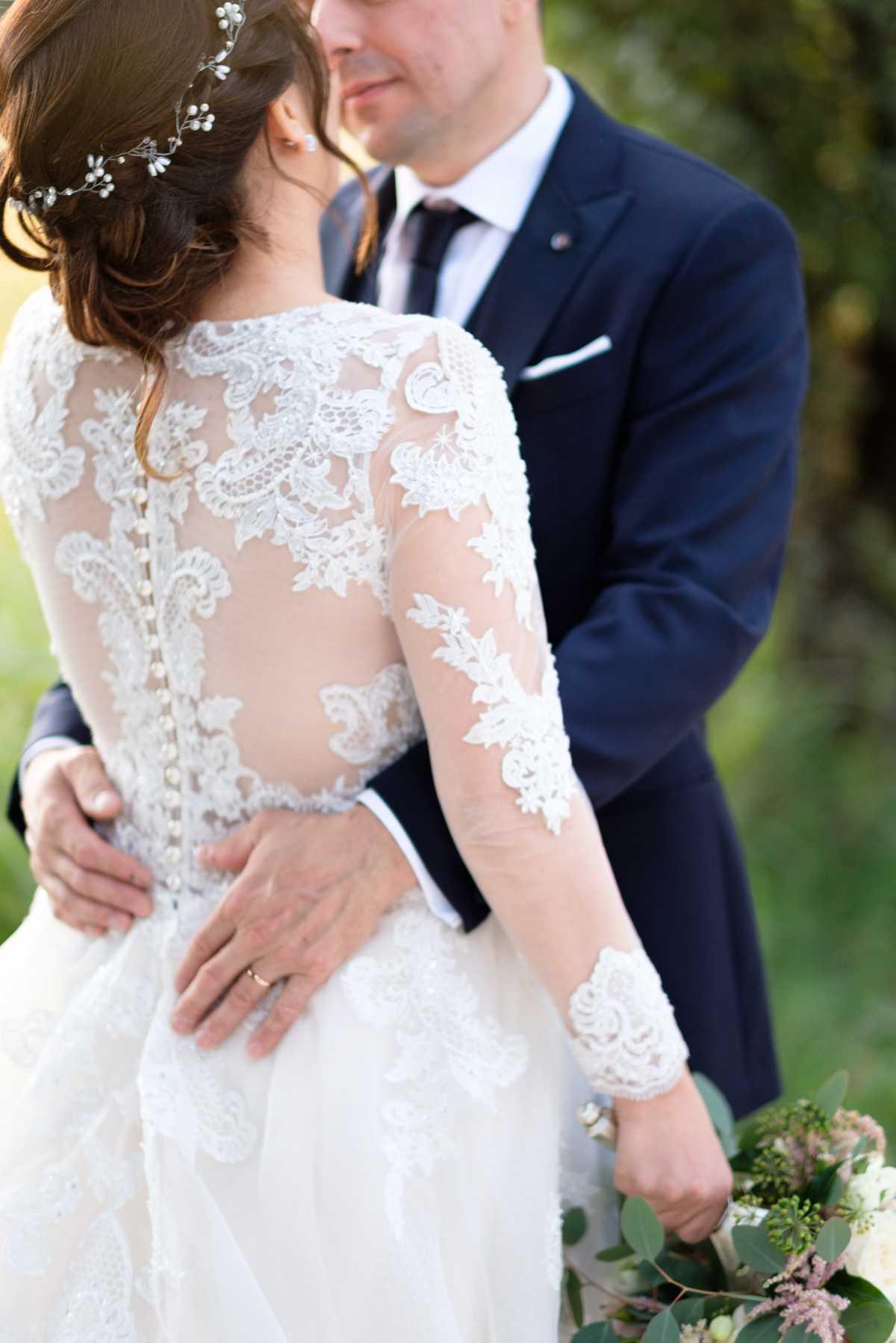 Fotografo di matrimoni a Verona coppia di sposi si abbraccia con abito in pizzo